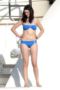 Anne Hathaway pondering the water on the aft of a motor yacht